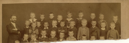 I think Leo must have been in the first row of this badly damaged photograph -- I can't find him among the kids who show. Based on the hairline, my money is on his head being the one right in front of the teacher. Date and photographer unknown.